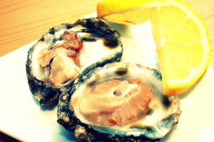 Freshly opened native oyster with a slice of lemon on the side. Sold online by Richard Haward's Oysters.