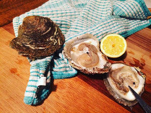 Native Oyster freshly opened with lemon slice. Sold online by Richard Haward's Oysters.