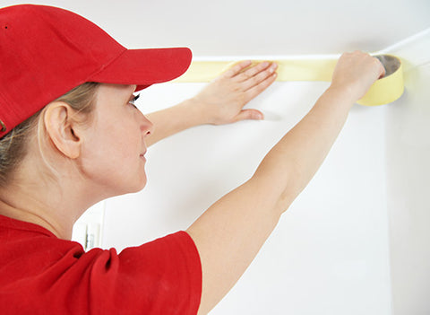 woman applying masking tape before using spray gun