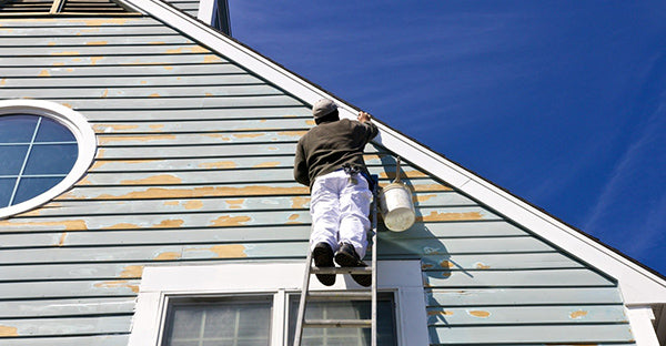 man preparing paint on exterior of house