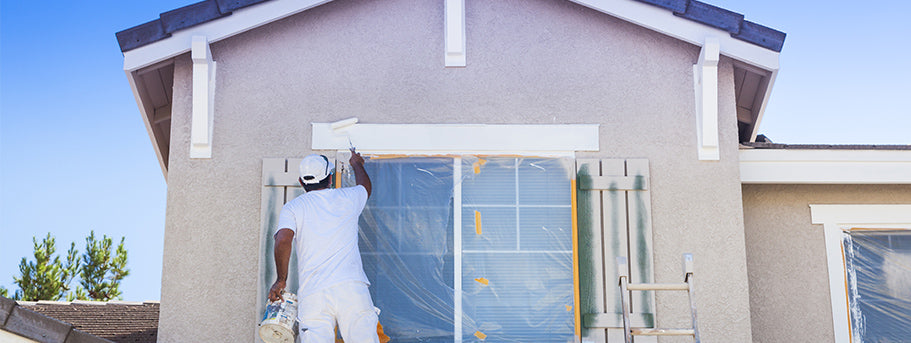 man painting exterior of house