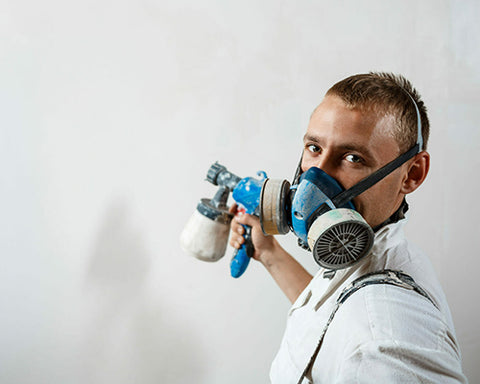 man painting wall with spray gun
