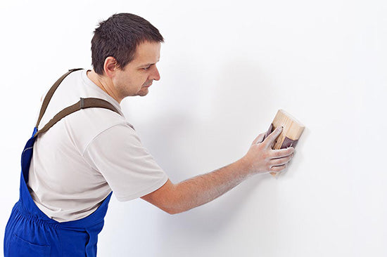 man sanding wall for paint preparation