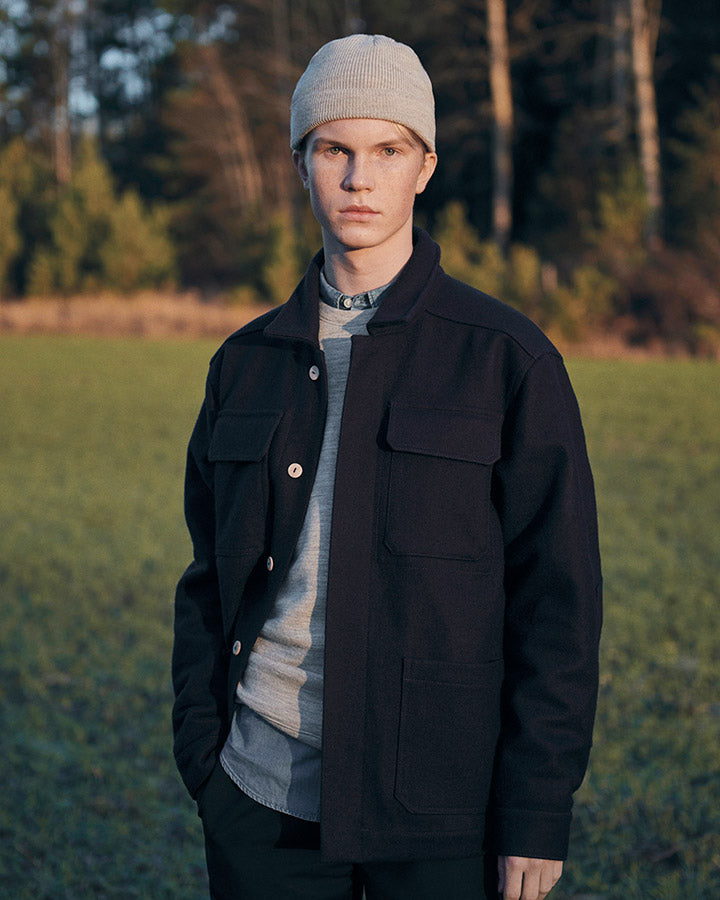 A man wearing a dark navy wool shirt jacket standing in front of a forest
