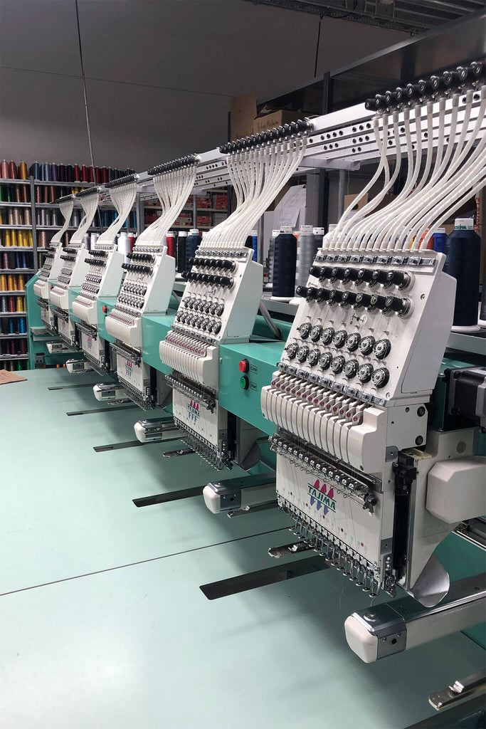 Embroidery machines sitting in a factory, with spools of colourful thread in the background