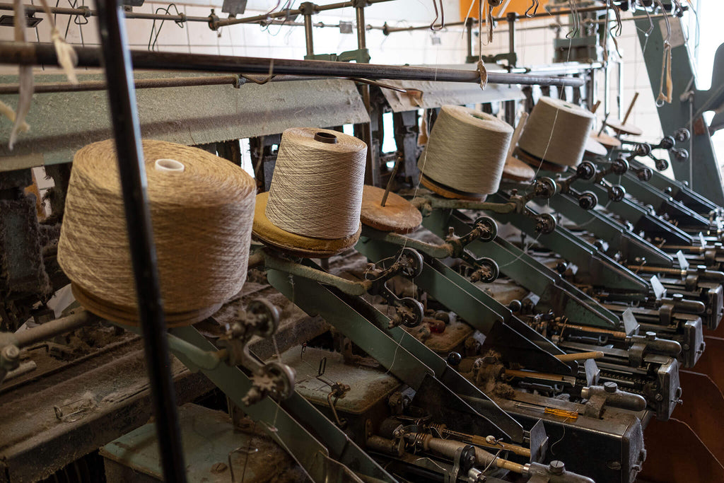 Heavy industrial machinery with spools of fabric lie still.