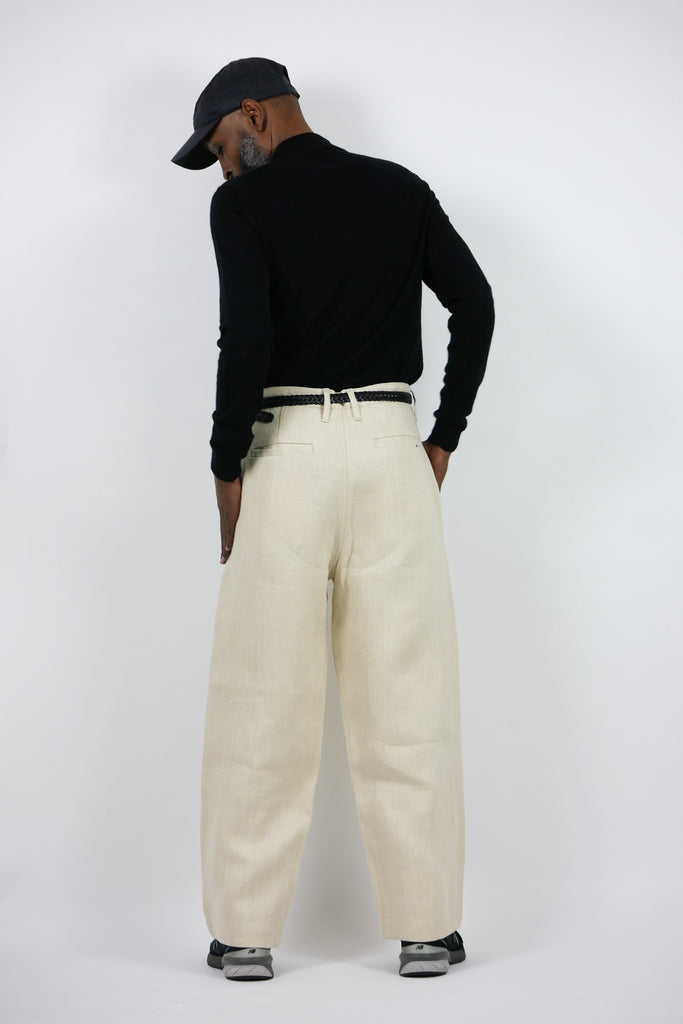 A man models a pair of white coloured jeans made from hemp.