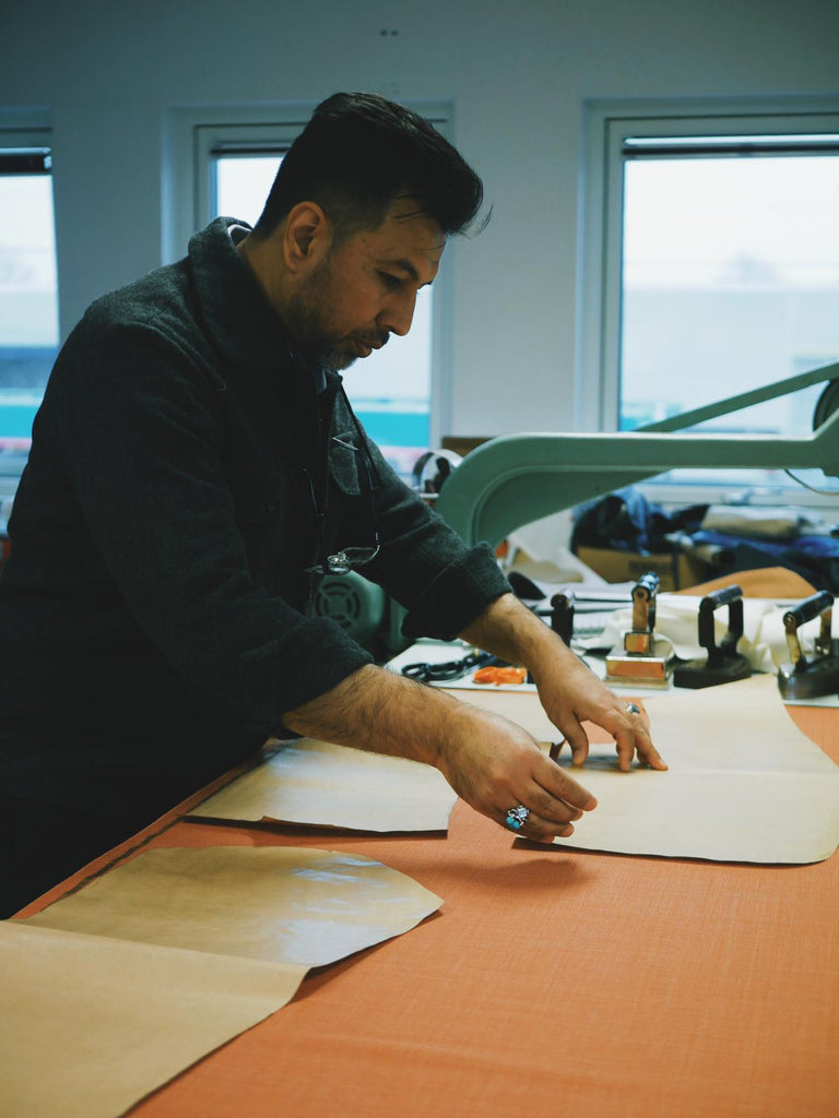 A tailor puts a template on a piece of fabric to prepare it for cutting.