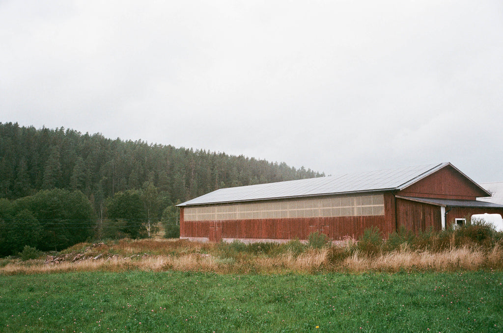 A barn in an open field, with hills in the background, with an array of solar panels on the roof