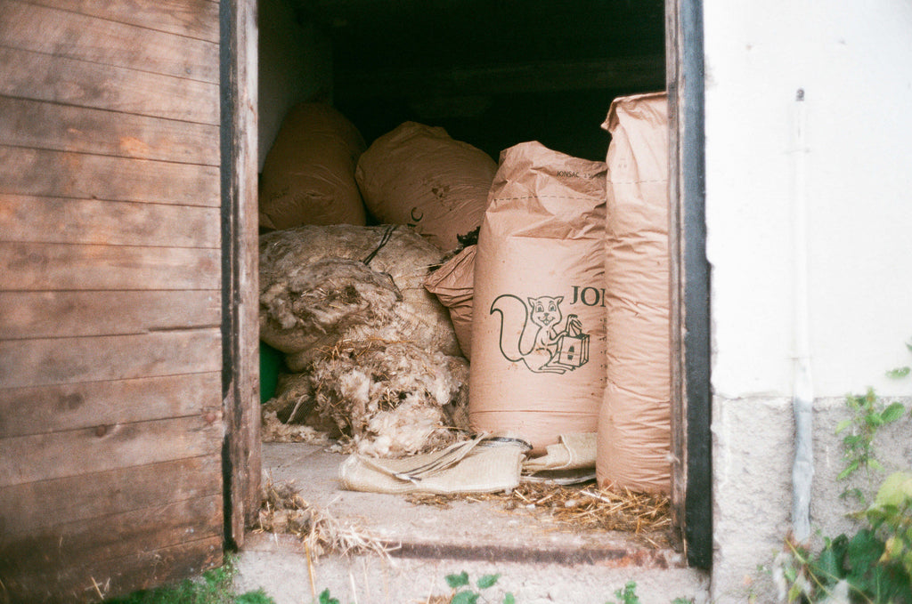 Large bags filled with old wool sitting in a barn.