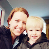 Auburn haired mother and blond preschooler smile together at home, dressed in winter jackets