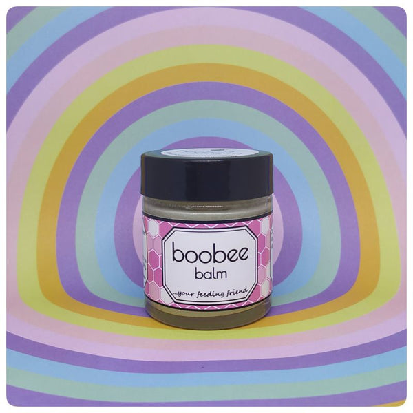 A pink labelled jar of soothing Boobee Balm sits on a psychedelic background of colourful circles