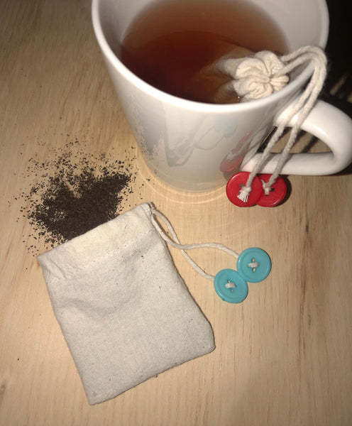 open cotton teabag with beaded drawstring, with loose tea spilling out, next to a cup of tea with a cotton teabag in it.