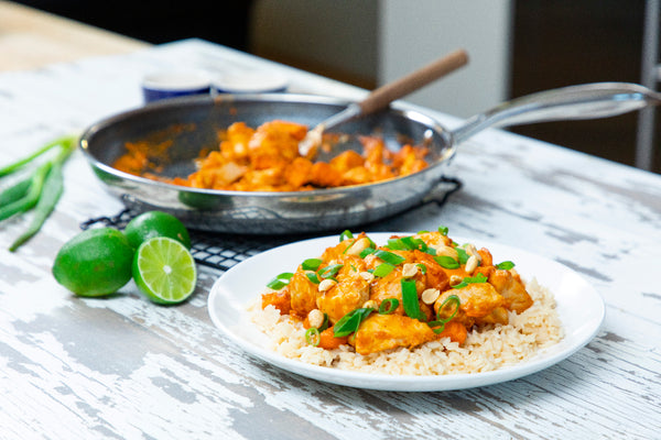 Coconut Curry Chicken and Sweet Potato next to Stainless Steel HexClad Pan