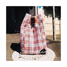Load image into Gallery viewer, upcycled urban shopper - good bag habit big iconic check red on manhole. sustainable bag brand. made in south africa.