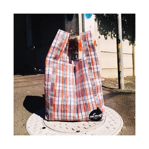 upcycled urban shopper - good bag habit big iconic check red on manhole. sustainable bag brand. made in south africa.