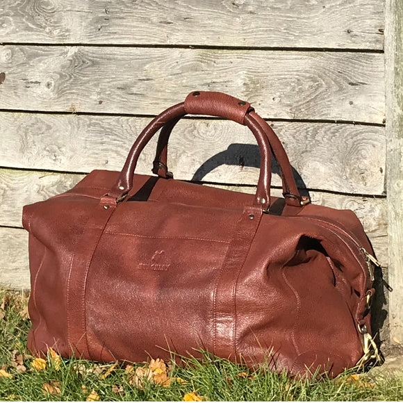 The Boston. A classic brown leather holdall by Burghley Bags. Handmade from finest, hardwearing grained leather. Features metal feet and comes with a shoulder strap.  Meets most airline carry-on requirements.