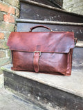 "The Dorrington Briefcase. A classic 30's styled leather briefcase by Burghley Bags. A handmade leather vintage work bag, with enough space for 15"" laptops. Comes with an adjustable and detachable shoulder strap. Shown in vintage brown."