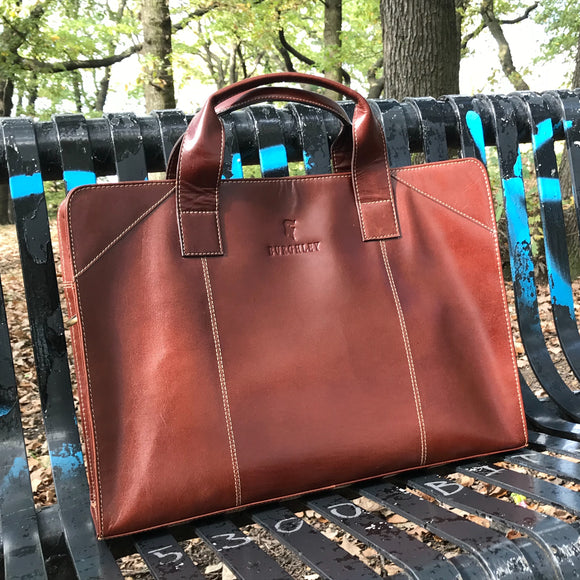 The Easton Briefcase. An elegant and modern work bag by Burghley Bags. Handmade from luxurious chestnut leather, it's large enough for 15