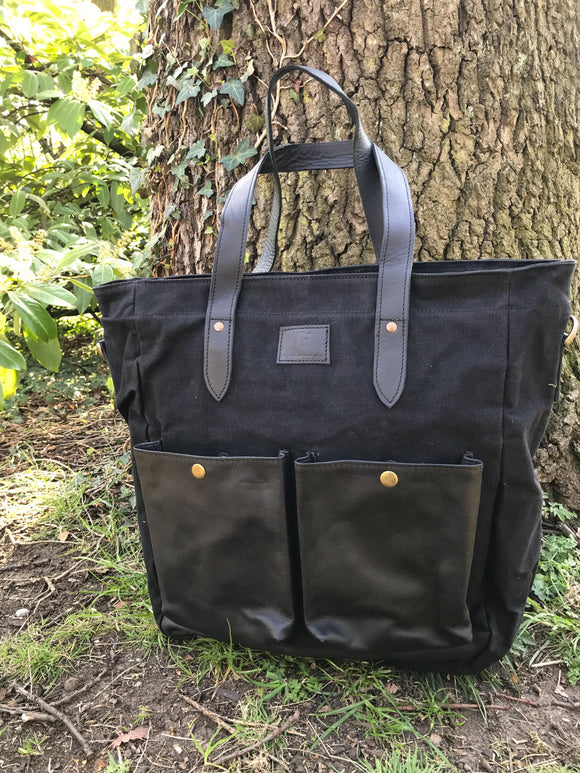 The Bingham.  A large zipped tote bag by Burghley Bags.  Handmade from eco-friendly vegetable tanned leather and strong cotton canvas, with a canvas shoulder strap. Shown in elegant black.