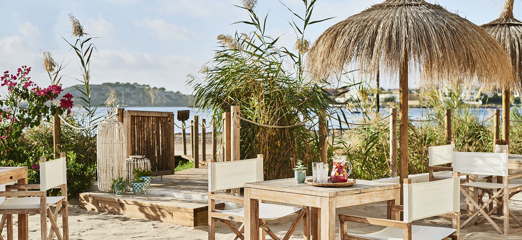 Rustic dining furniture and a natural-fibre parasol on a beach in Ibiza