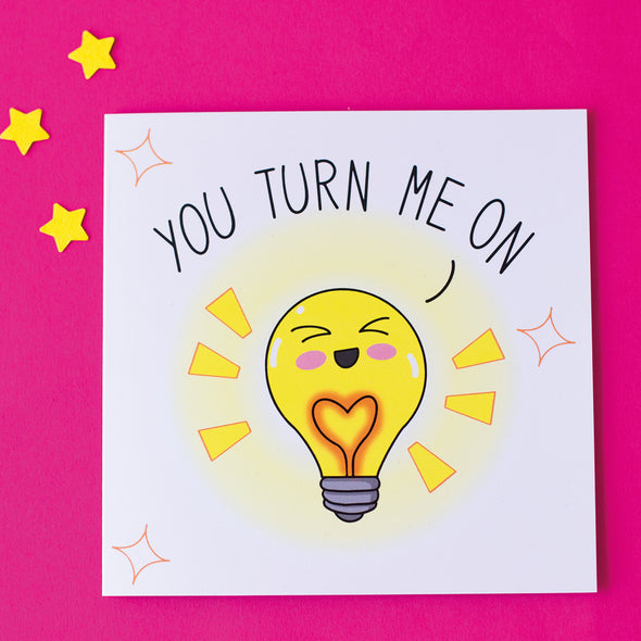 Funny valentine's anniversary card. Cute illustration of a lightbulb saying you turn me on. sat on a pink background with yellow stars
