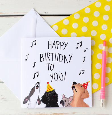 Dogs signing Happy Birthday to you. A whippet, Black cockapoo with a party hat, french bulldog and Golden Retriever with a party hat. Illustrated by fizzijayne. Comes with a white envelope and packed in a candy bag