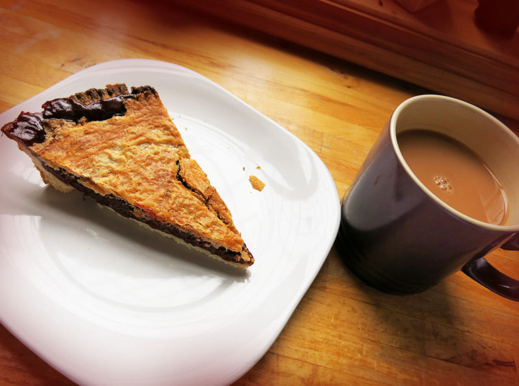 one piece of cherry pie on a plate with a hot cup of tea next to, the perfect combination