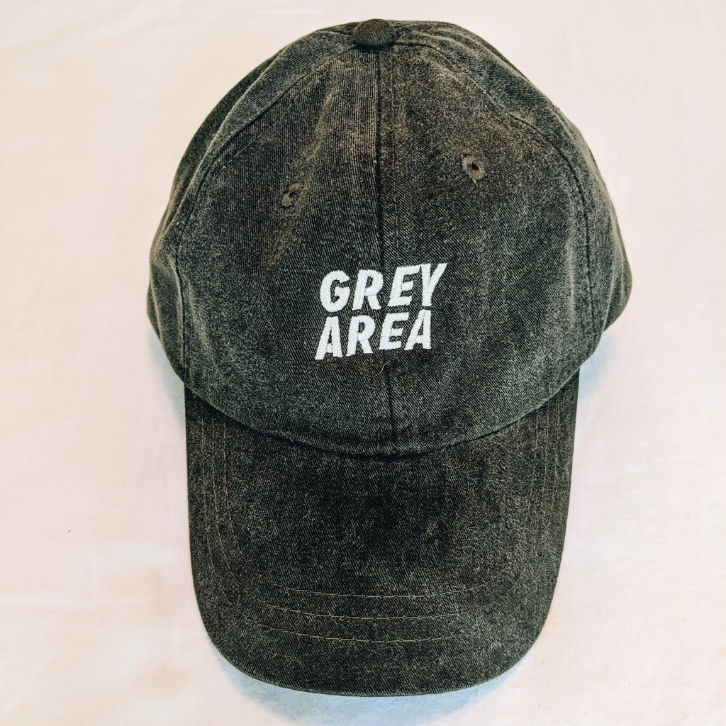 "Unstructured dad hat with curved brim, leather strapback with brass clasp. Hat reads ""Grey Area""."