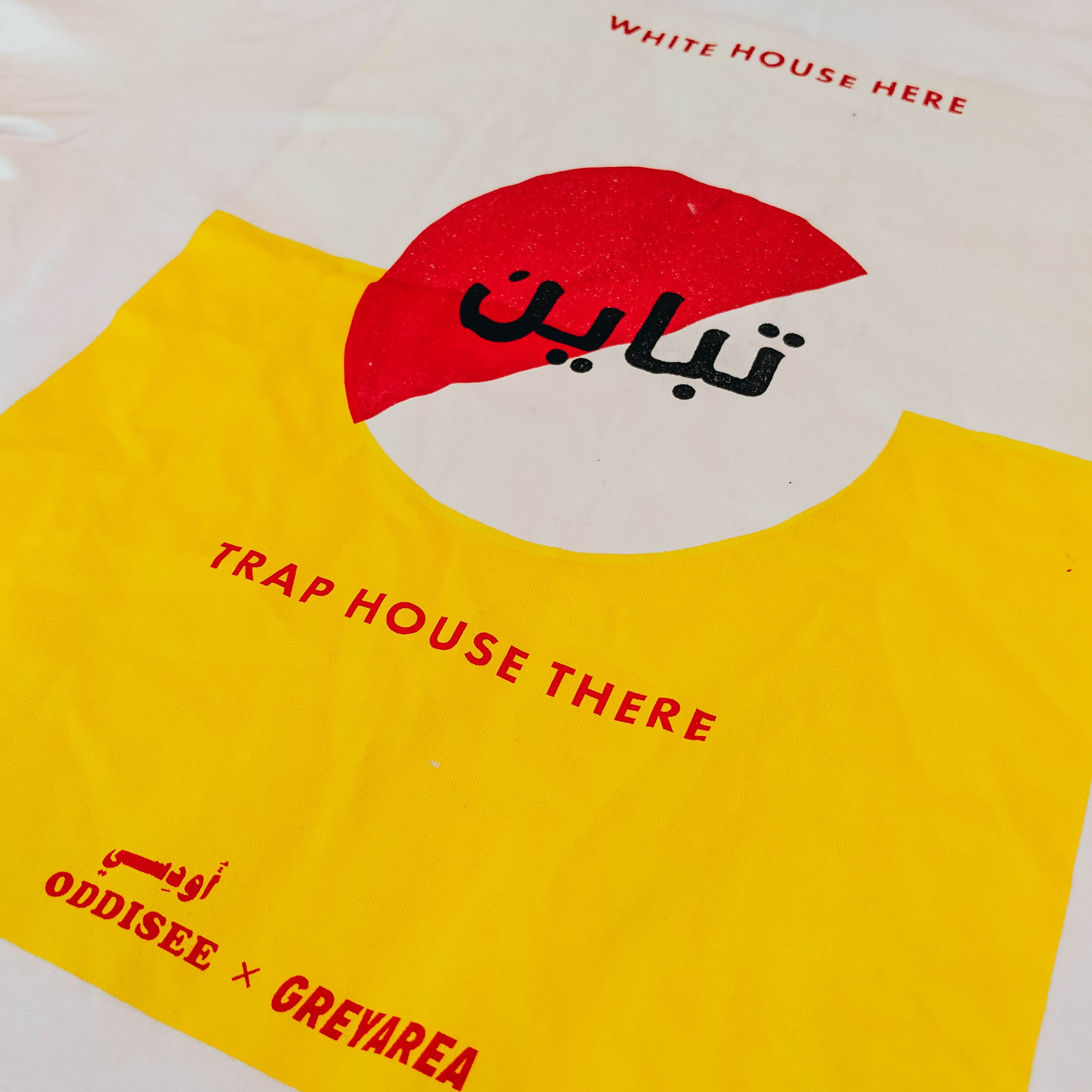 "Abstract graphic on the back reading ""White House here, trap house there."" Arabic characters reading ""Contrast""."