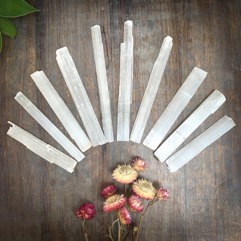 Selenite sticks fanned across table with flowers