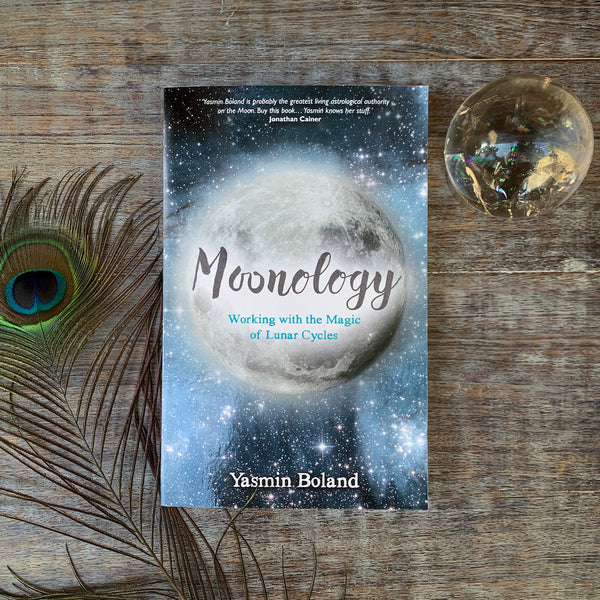 Moonology book by Yasmin Boland with clear quartz orb and peacock feather