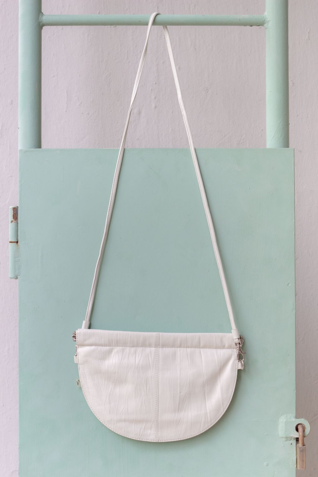 half moon crossbody bag in white in front of mint wall