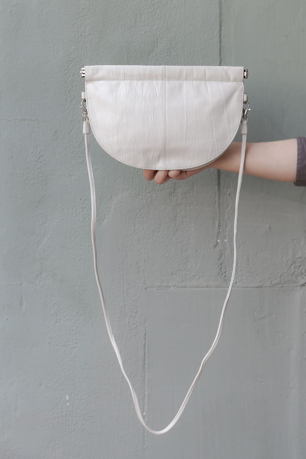 half moon crossbody bag in white  in front of grey wall