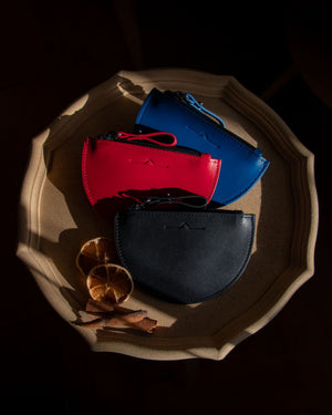 half moon mini leather pouch in 3 colour: blue, red and black with sun-dried orange slide in Christmas vibes
