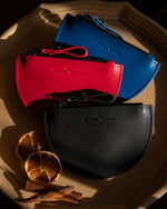 half moon mini leather pouch in 3 colour: blue, red and black with sun-dried orange slide in Christmas vibes close up