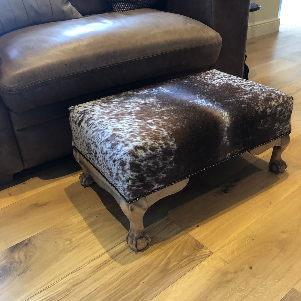 Cowhide footstool with antique oak ball and claw feet
