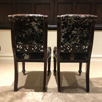 Pair of carved mahogany chairs upholstered in brown and white cowhide