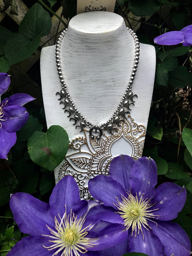 Silver Necklace on Display with Purple Flowers