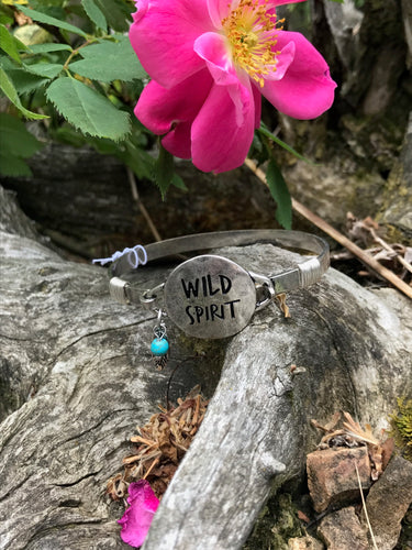 Wild Spirit Bangle Bracelet with Turquoise Charm on Rustic Background with Flower