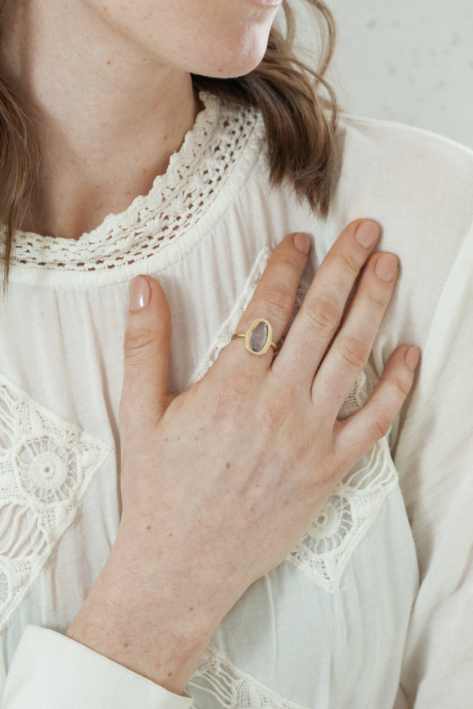 Model wearing Handmade freeform blue sapphire ring in 18kt gold.