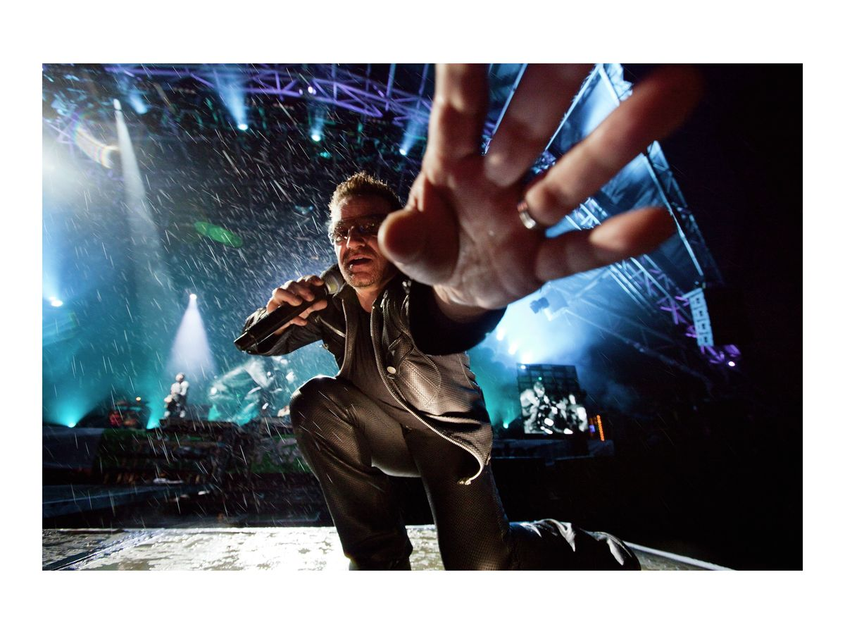 Bono reaches out to take David Levene's camera, 2011