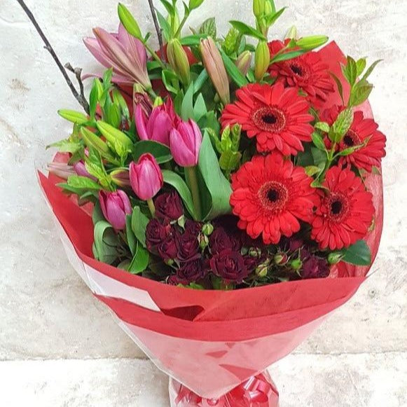 A beautiful bouquet of red flowers with tulips, gerberas and lilies