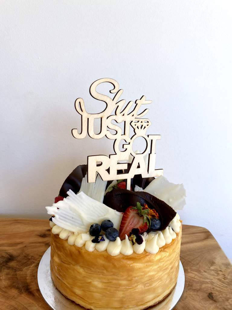 Wooden 'Shit Just Got Real' Engagement Cake Topper
