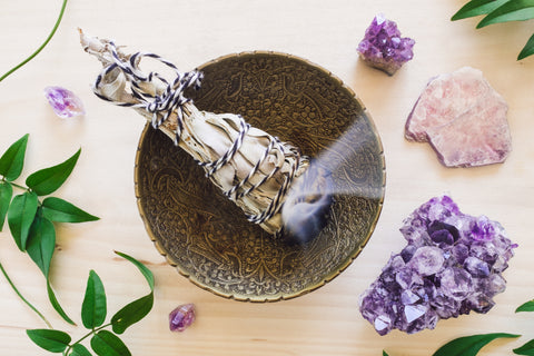 Lit Sage Smudge Sticke in Decorative Brass Bowl Surrounded by Amethyst Crystals