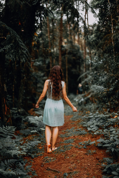 Barefoot woman walking on forest path