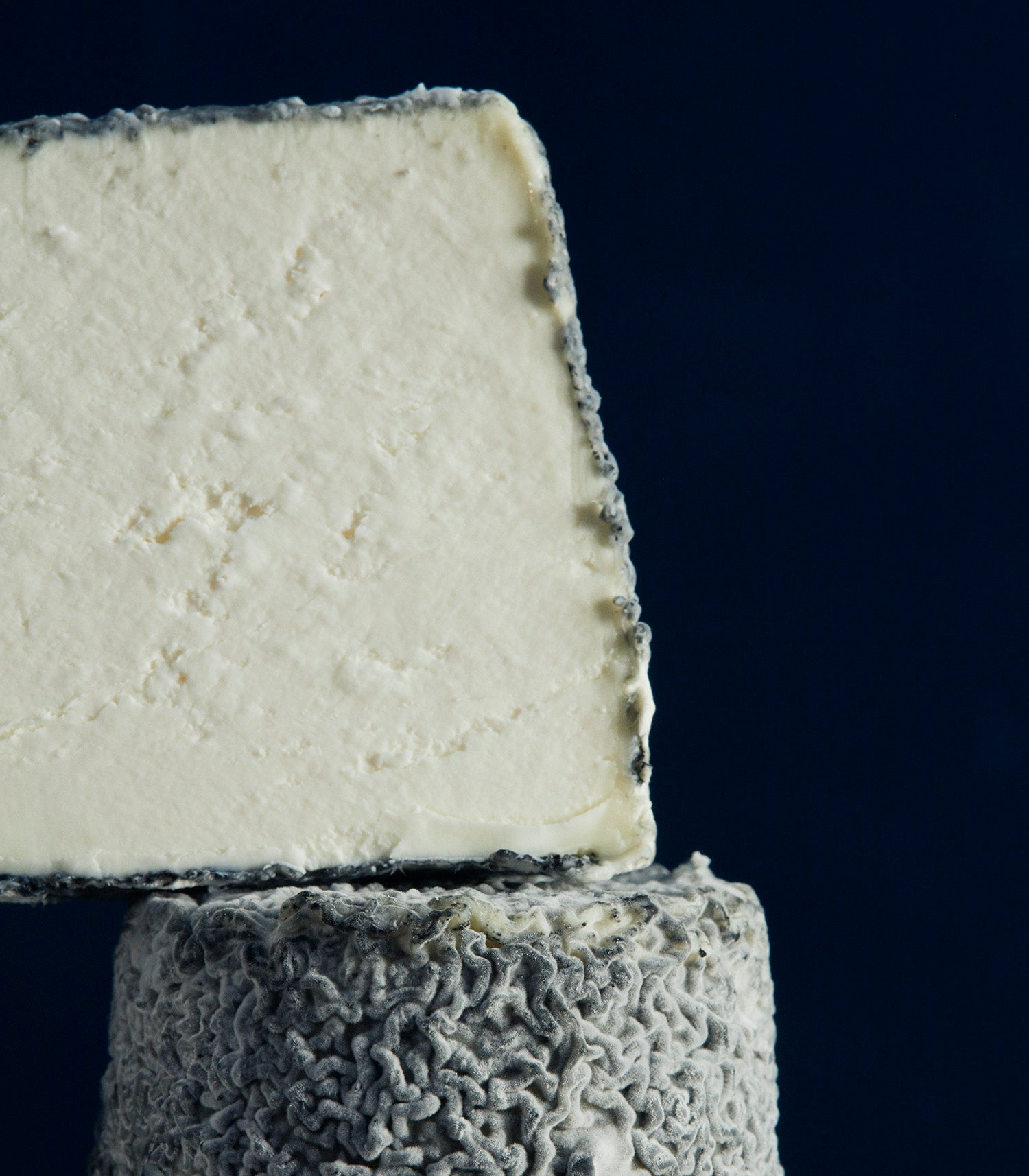 Close up of a cut turret-shaped Dorstone goat's cheese with a mould-covered grey wrinkly rind and delicate white paste