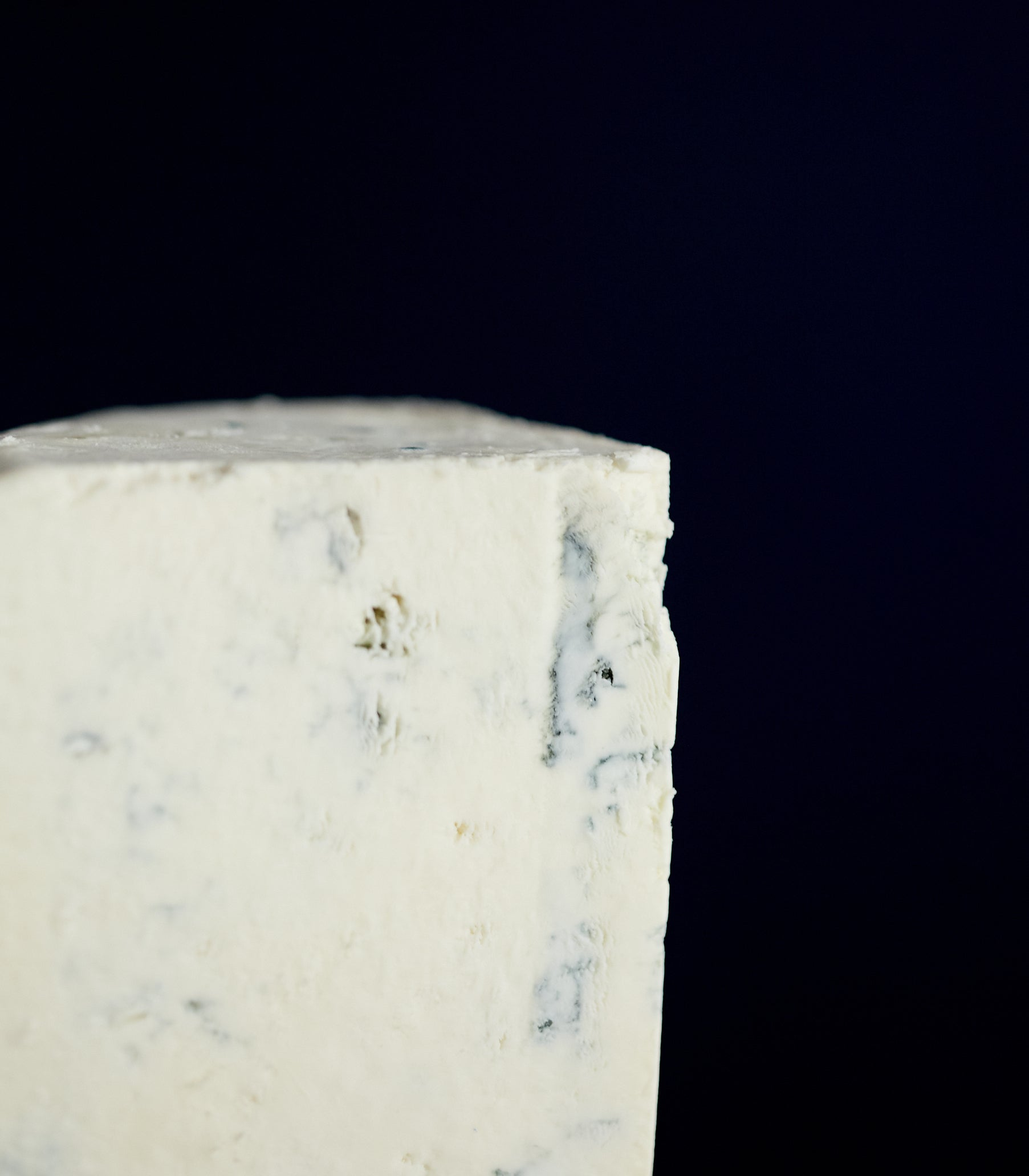 Close up of a cut piece of Harbourne Blue vegetarian goat's milk cheese showing the light blue veining and a crumbly texture