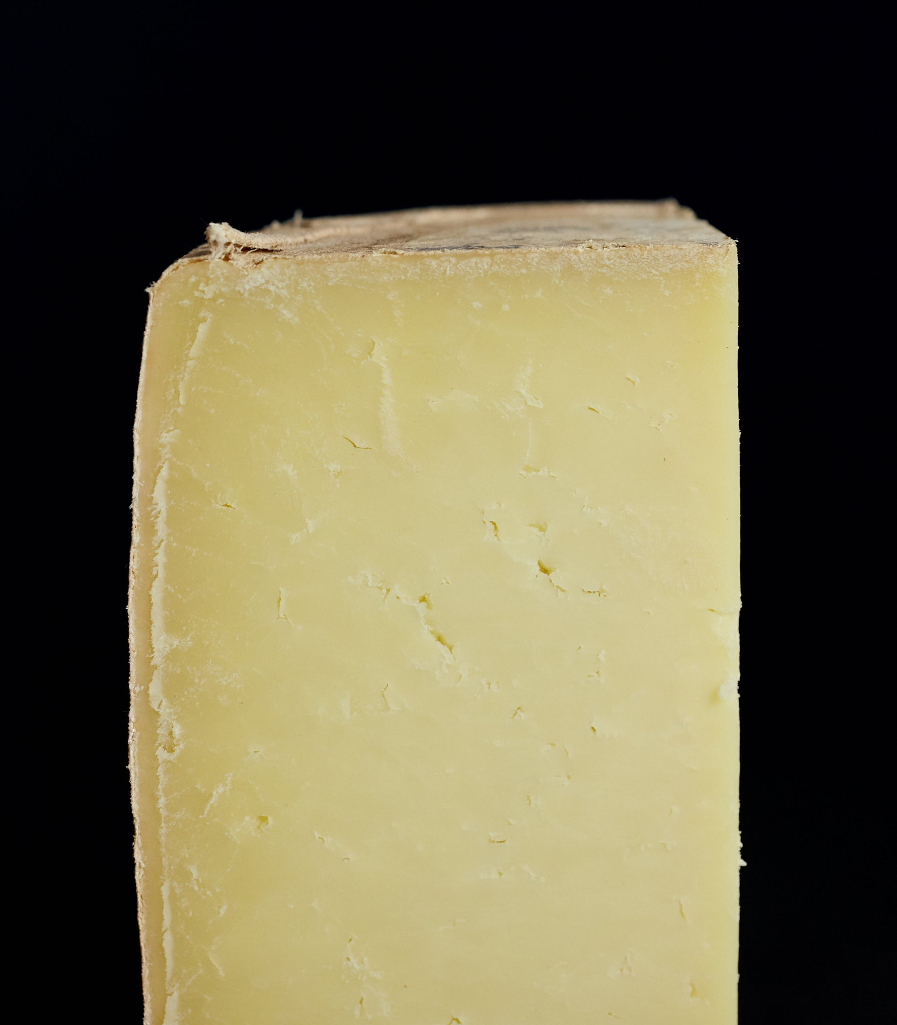 Close up of a cut quarter clothbound Corra Linn sheep's milk cheese with creamy, succulent paste