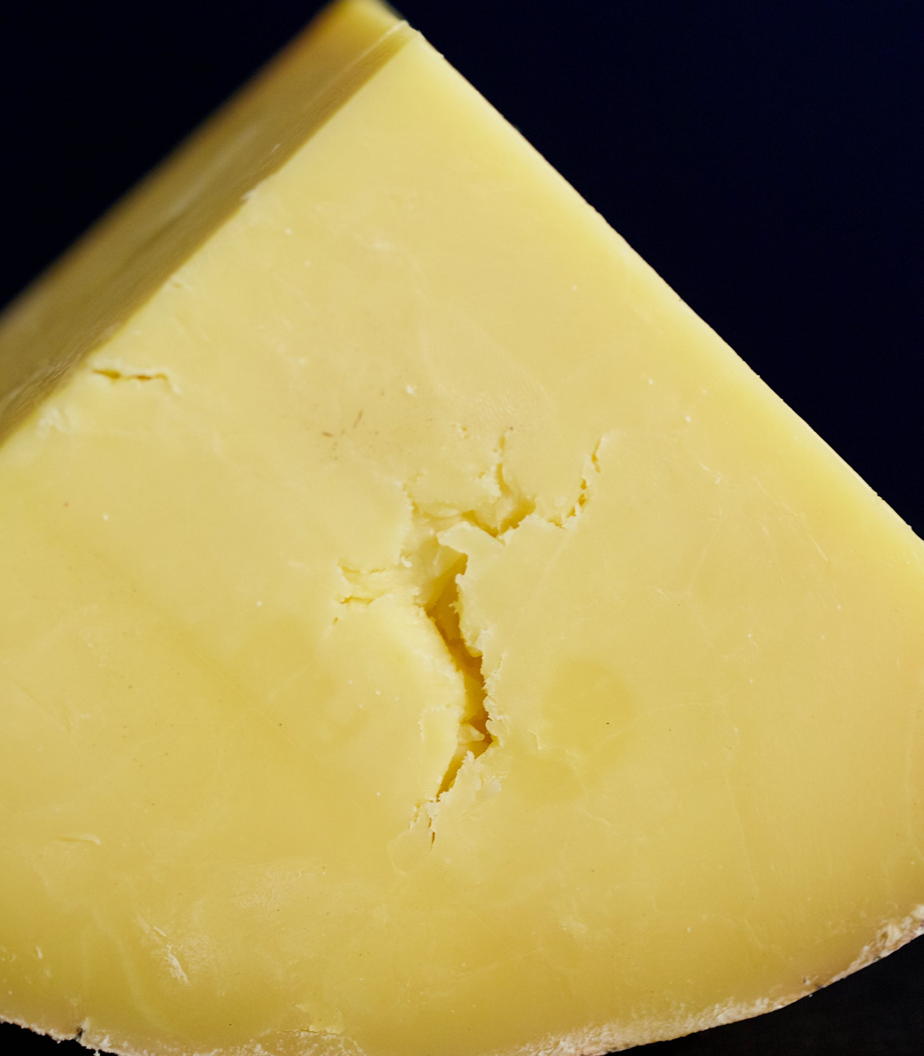 Close up of a large cut of clothbound Hafod Cheddar cheese showing the texture of the golden paste